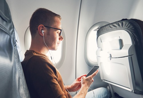 customizable solutions. man on a plane with earbuds.