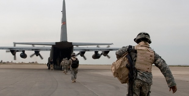 an equipped soldier heading to an airplane