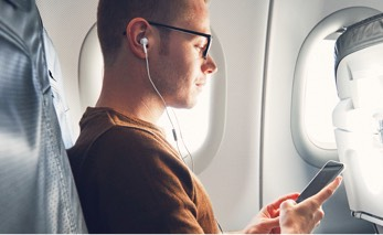 a man sitting on a plan with earbuds on